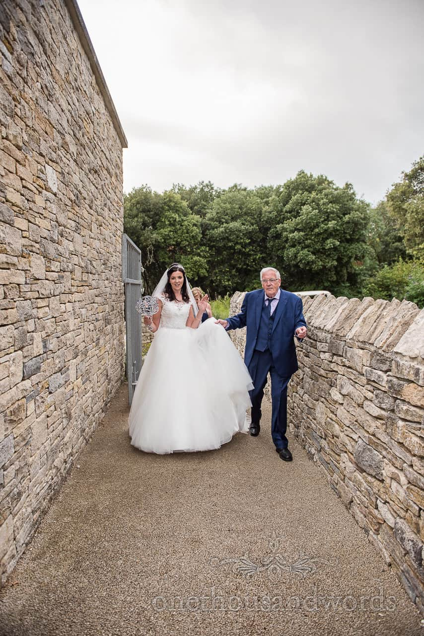 Bride and father dance as they walk to Purbeck castle wedding ceremony