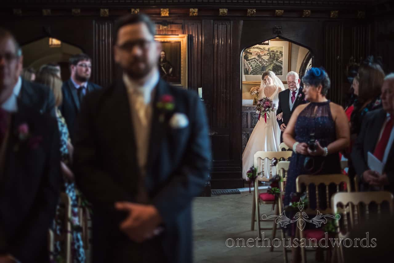 Bride and father enter Athelhampton House during wedding ceremony by one thousand words photography