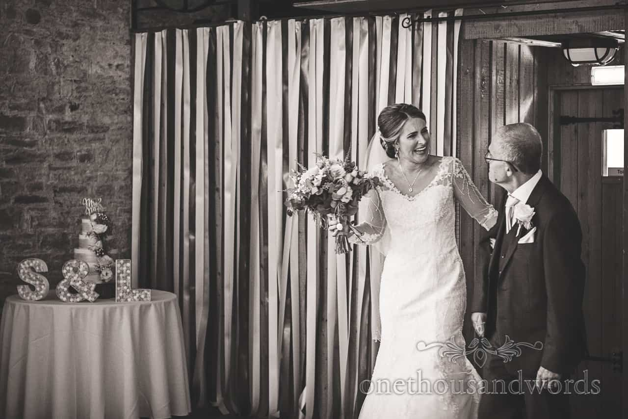 Black and white documentary wedding photograph of laughing bride and father wedding entrance at Kingston barn wedding photograph