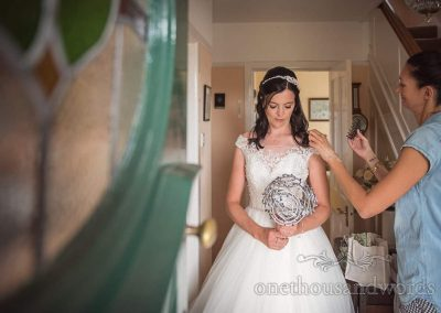 Bride has final adjustments before leaving house on wedding morning in Swanage