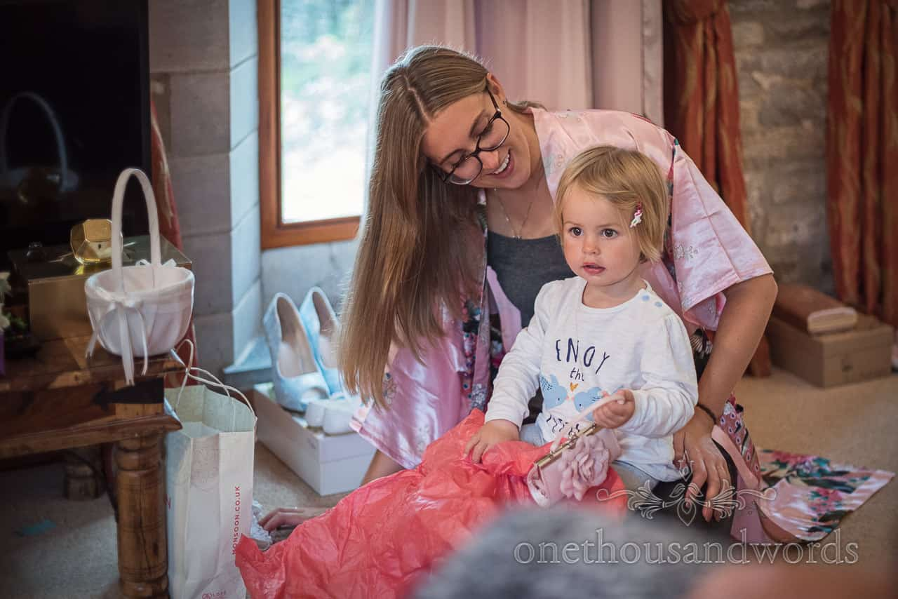Happy bride opens present with cute flower girl daughter during wedding morning preparation photographs