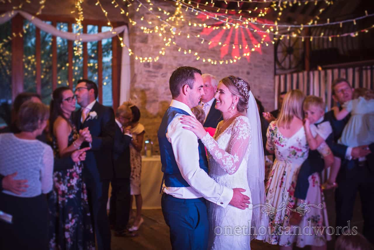 Bride and groom in the centre of the dance floor under disco and fairy lights at Kingston barn wedding photographs