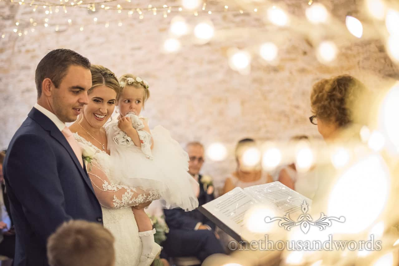 Bride and groom with daughter during civil wedding ceremony at Kingston Country Courtyard from Kingston barn wedding photographs