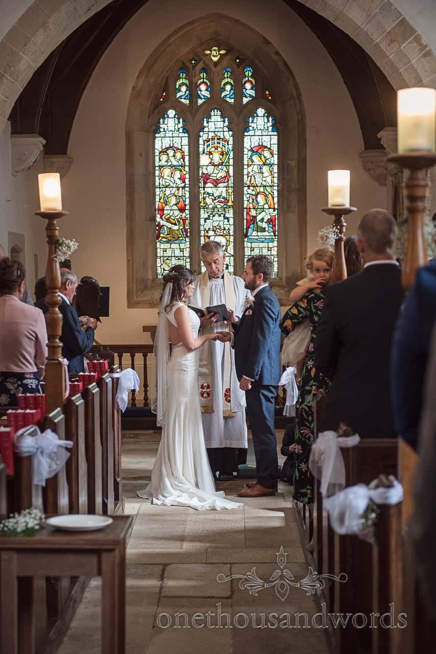 Bride and groom holf hands as they exchange marriage vows during a Dorset church wedding ceremony