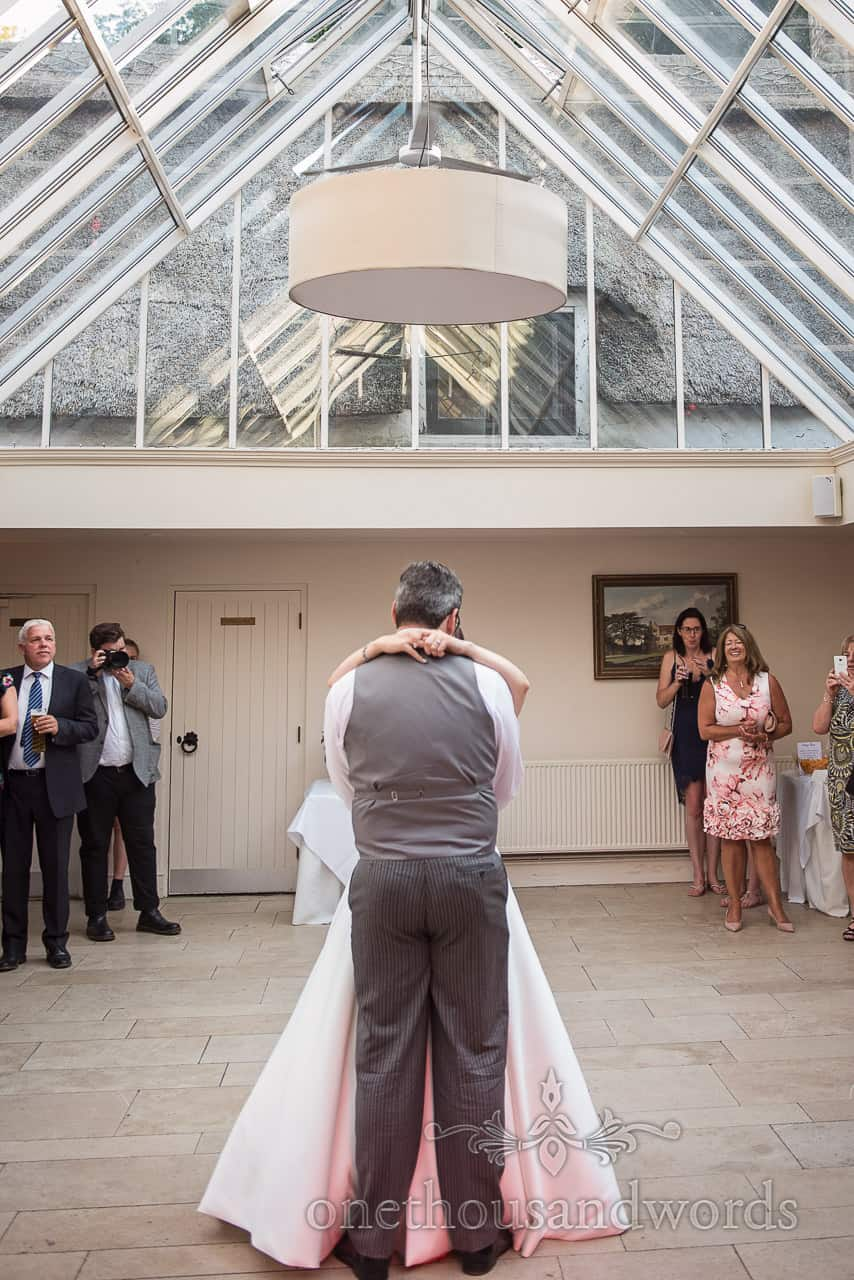 Bride and groom take first dance during coach house reception at Athelhampton House