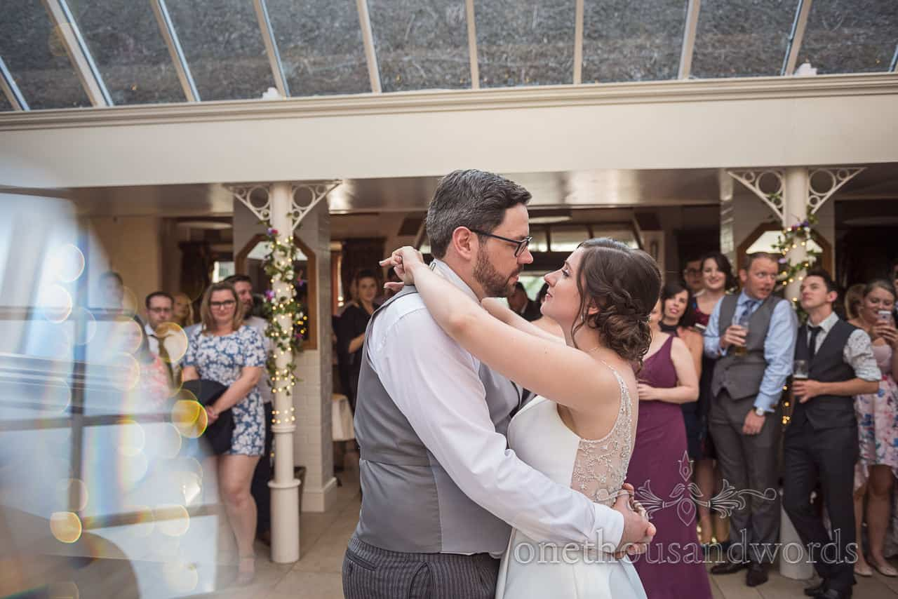 Bride and groom dance first dance watched by wedding guests Athelhampton House by one thousand words photography