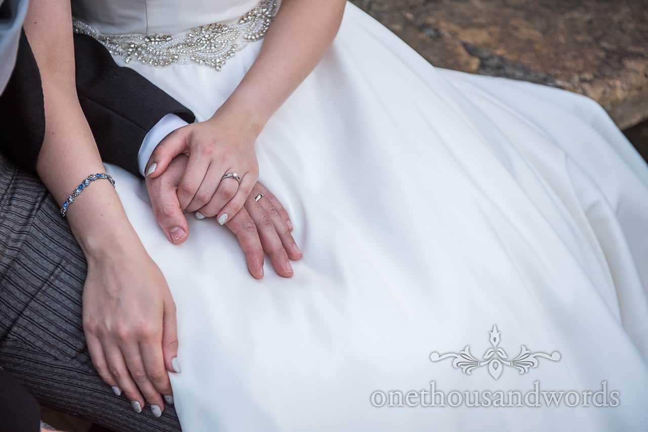 Bride and groom hold hands on laps during wedding evening by one thousand words photography