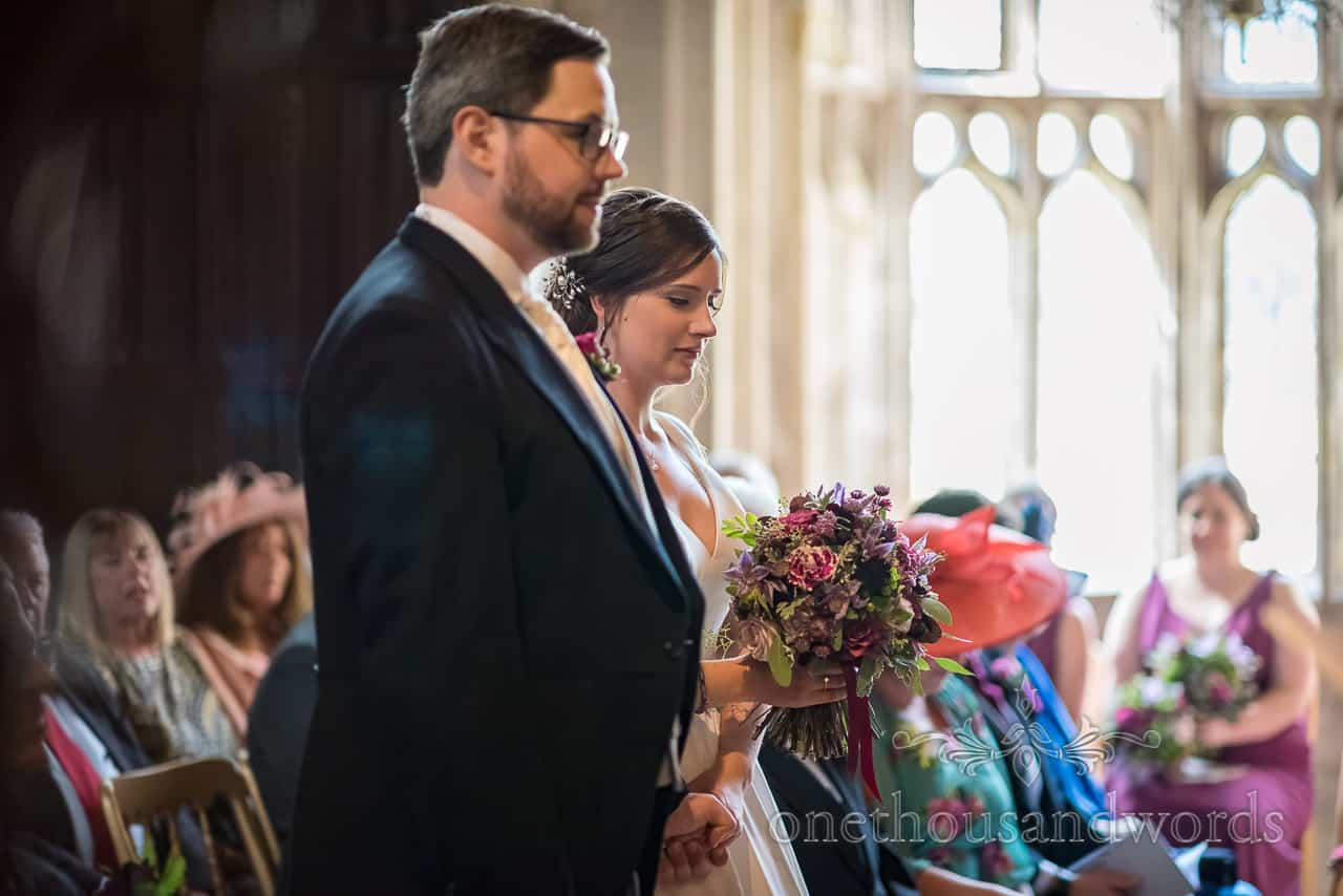 Bride and groom hold hands during wedding ceremony Athelhampton House by one thousand words photography