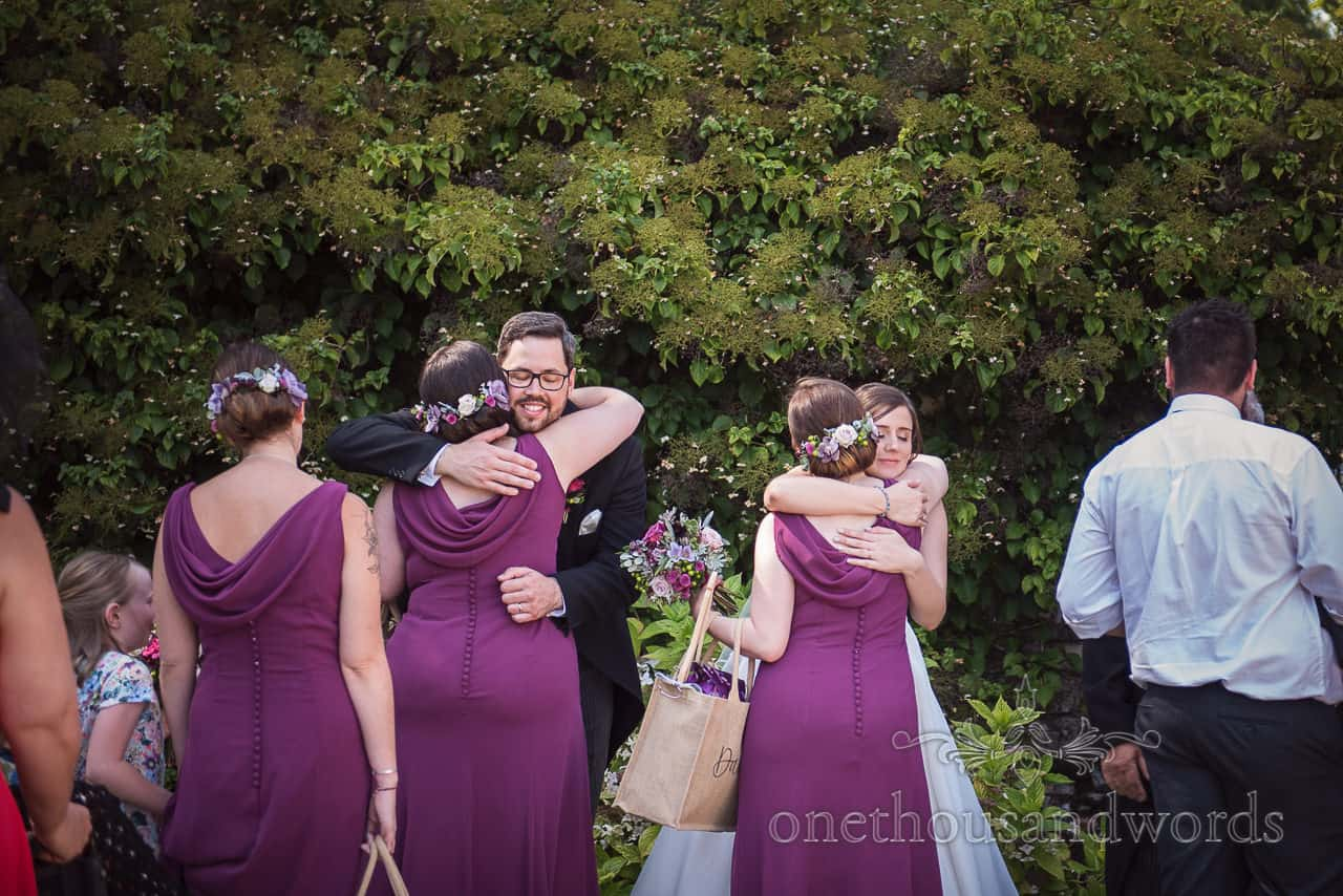 Bride and groom hug bridesmaids in purple dresses during receiving line by one thousand words photography