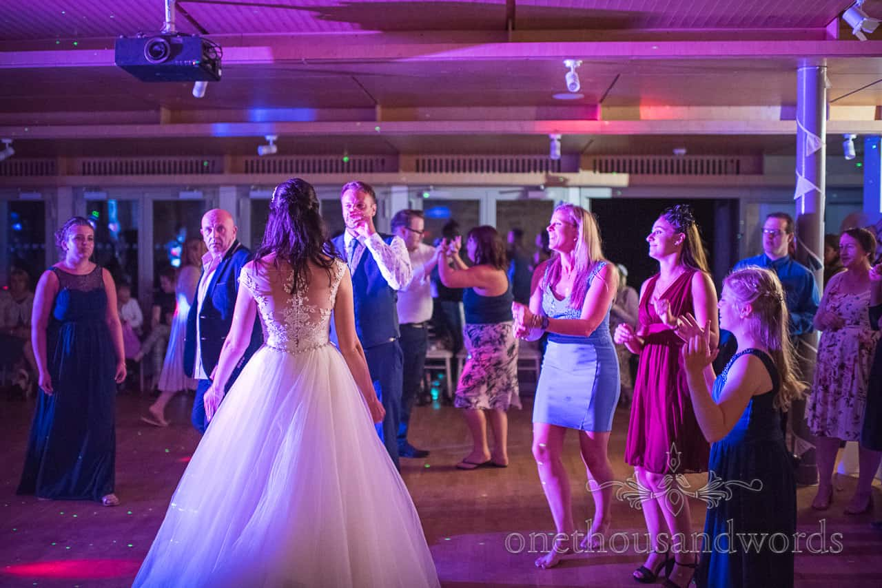 Bride and groom join wedding guests under blue and pink lights on dance floor at Durlston Castle wedding photographs
