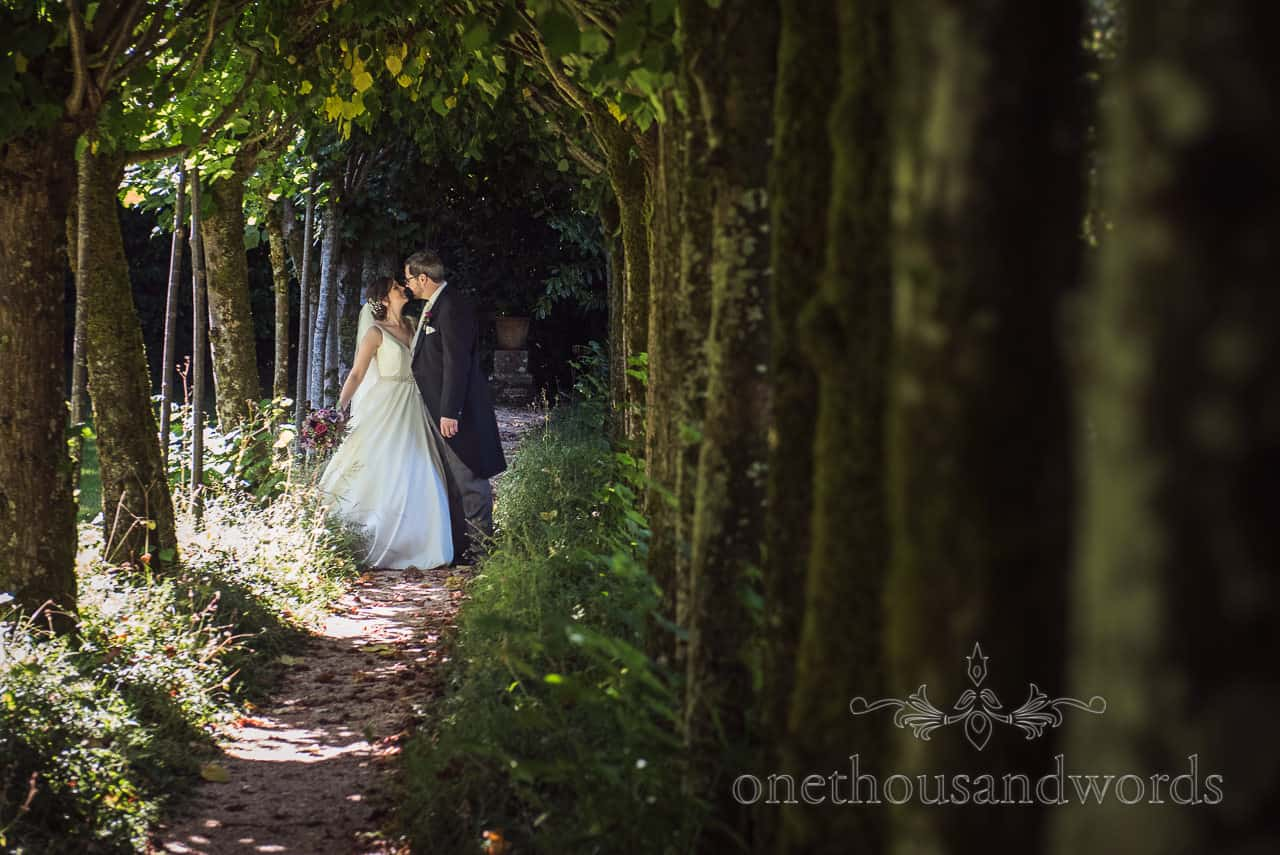 Bride and groom kiss in garden tree tunnel at Athelhampton House wedding