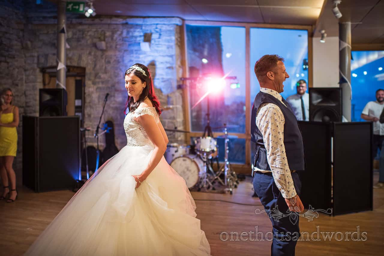 Bride and laughing groom start first dance choreographed routine with pink disco light at Durlston Castle wedding evening