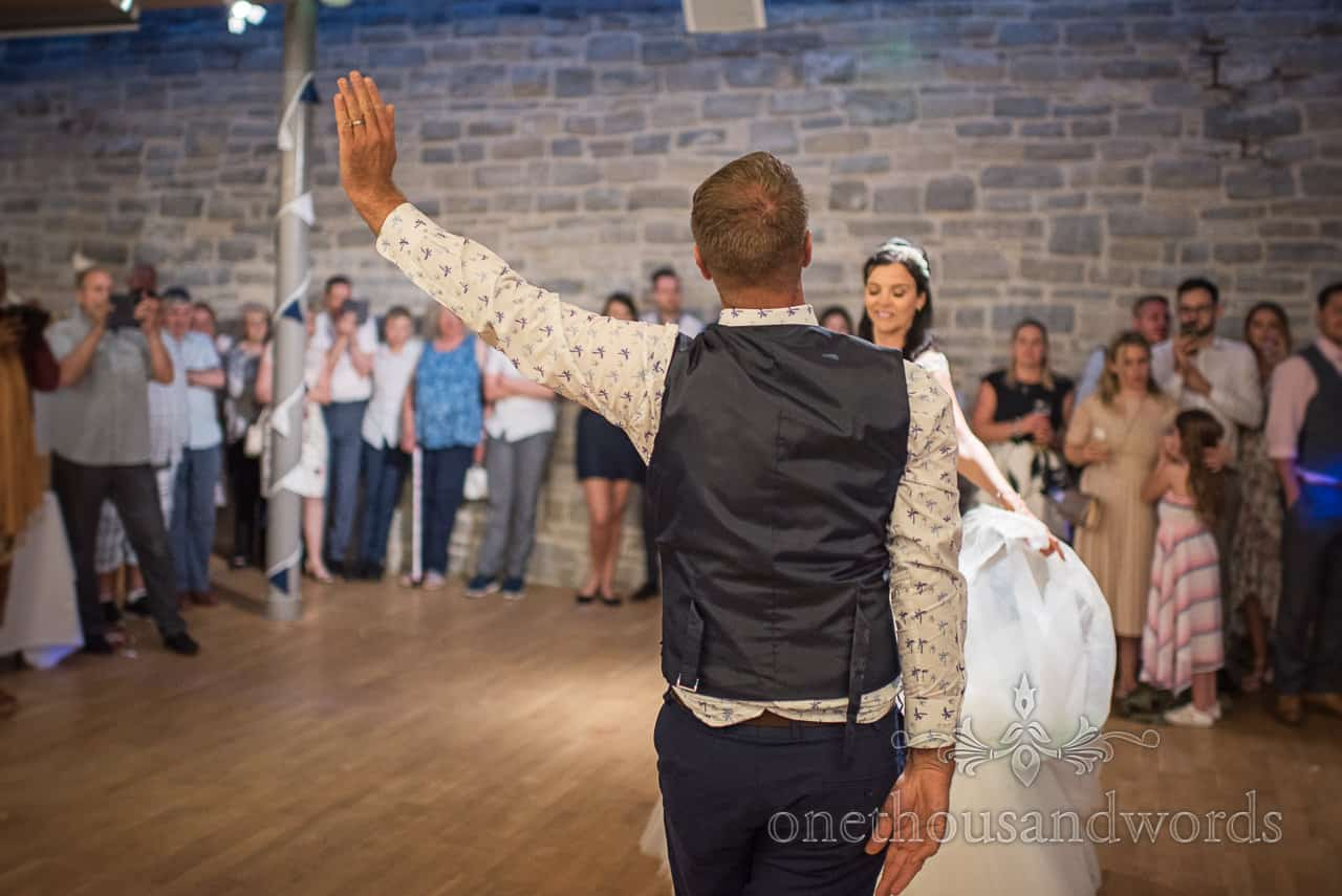 Bride and groom strike a pose during choreographed first dance routine on dance floor surrounded by wedding guests