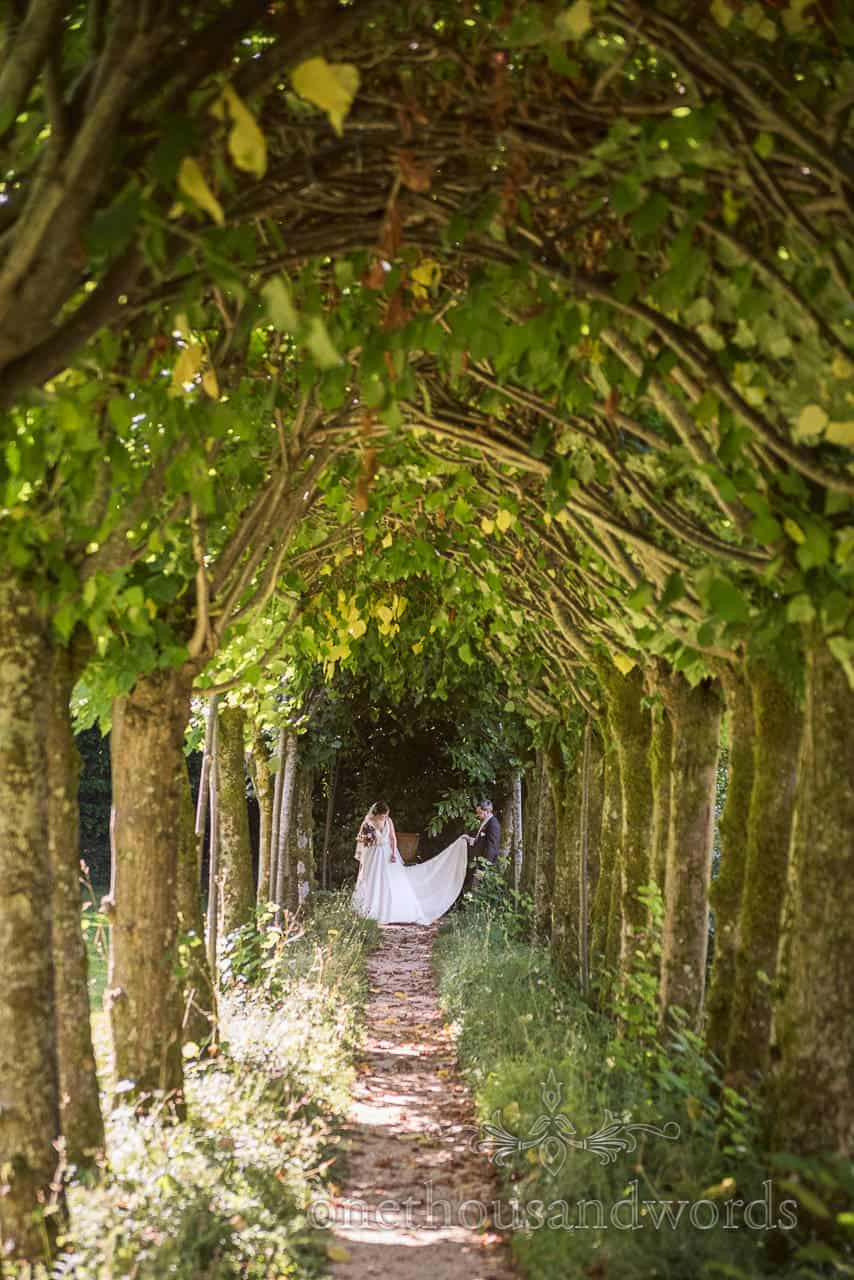 Bride And Groom At End Of Tree Tunnel In Garden At Athelhampton House Wedding Venue In Dorset