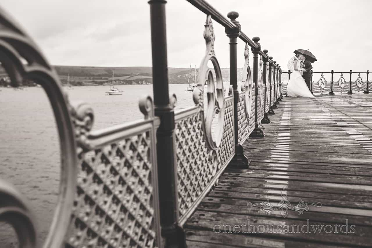Bride and groom kiss under umbrellas during Swanage Victorian Pier black and white wedding photos by one thousand words photography