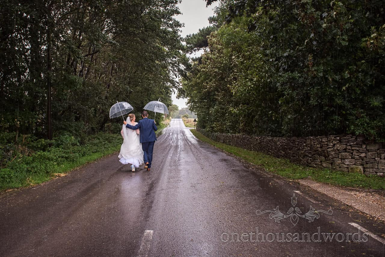 Rainy wedding photograph of bride and groom walking in the rain on a countryside road whilst holding clear plastic umbrellas