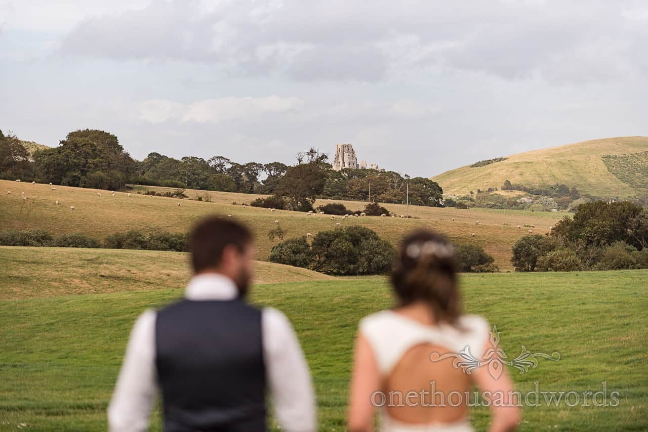 Bride and groom walk through countryside fields towards Corfe Castle during their Purbeck farm marquee wedding photographs