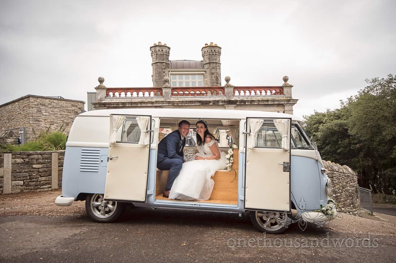Bride and groom sit in classic split screen VW wedding camper van at Durlston Castle wedding venue in Dorset