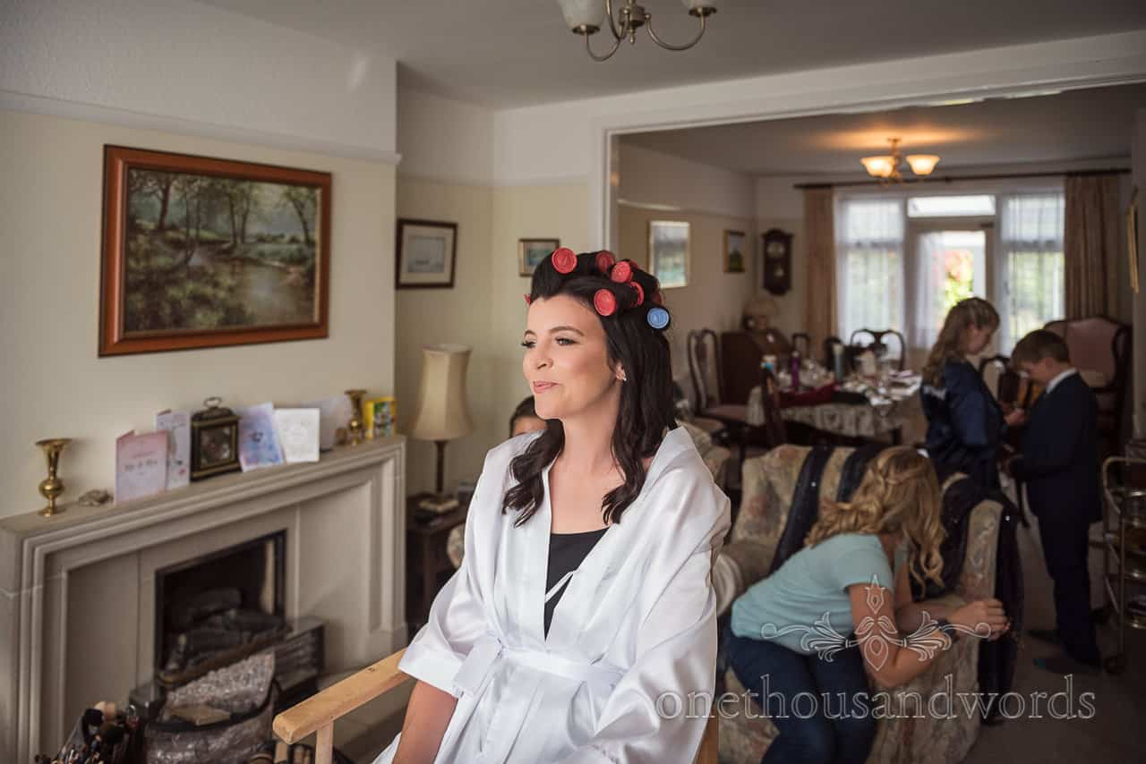 Happy bride with hair in curlers sits in natural light waiting for hair dresser during wedding morning preparations