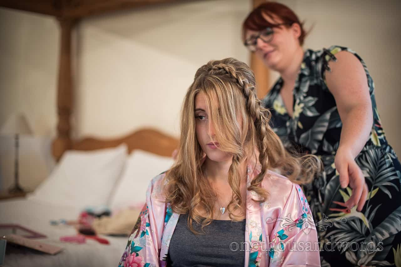 Sombre bride has wedding hair styled whilst wearing pink silk dressing gown on wedding morning in Dorset