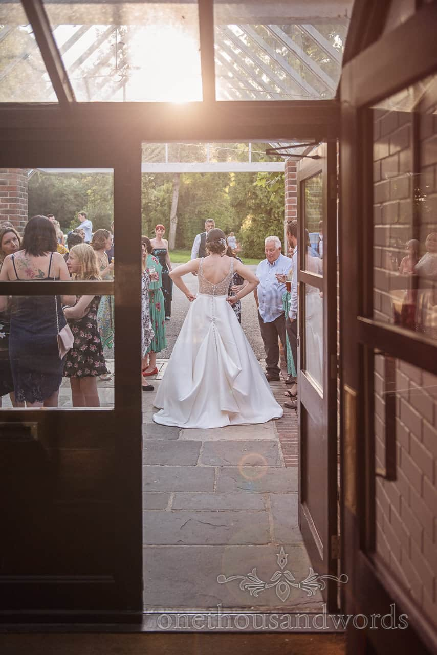 Bride with hands on hips talking to wedding evening guests at Athelhampton House by one thousand words photography