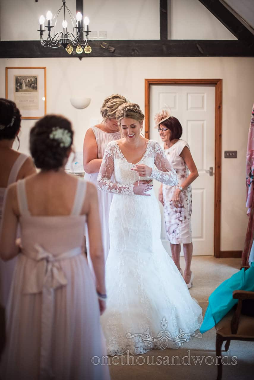 Bride is helped into white wedding dress during wedding morning preparations at Kingston Country Courtyard wedding venue in Dorset