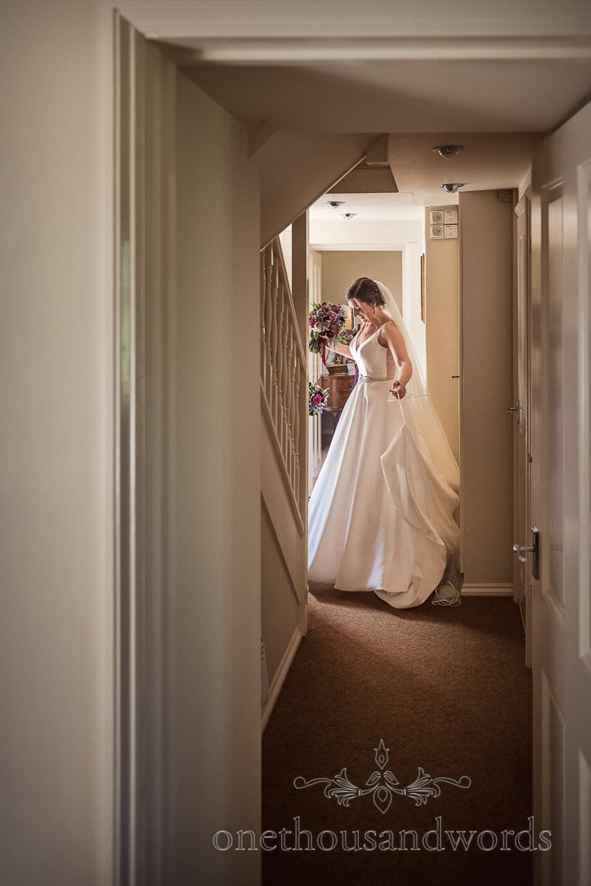 Bride in A line white wedding dress leaves wedding morning cottage documentary wedding photograph by one thousand words