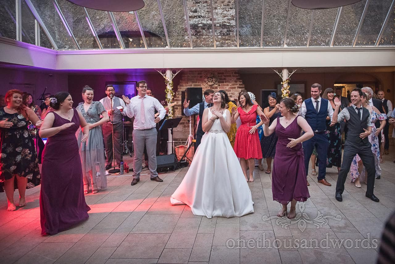 Bride joins in with surprise song and dance performance at Coach House reception at Athelhampton House wedding venue