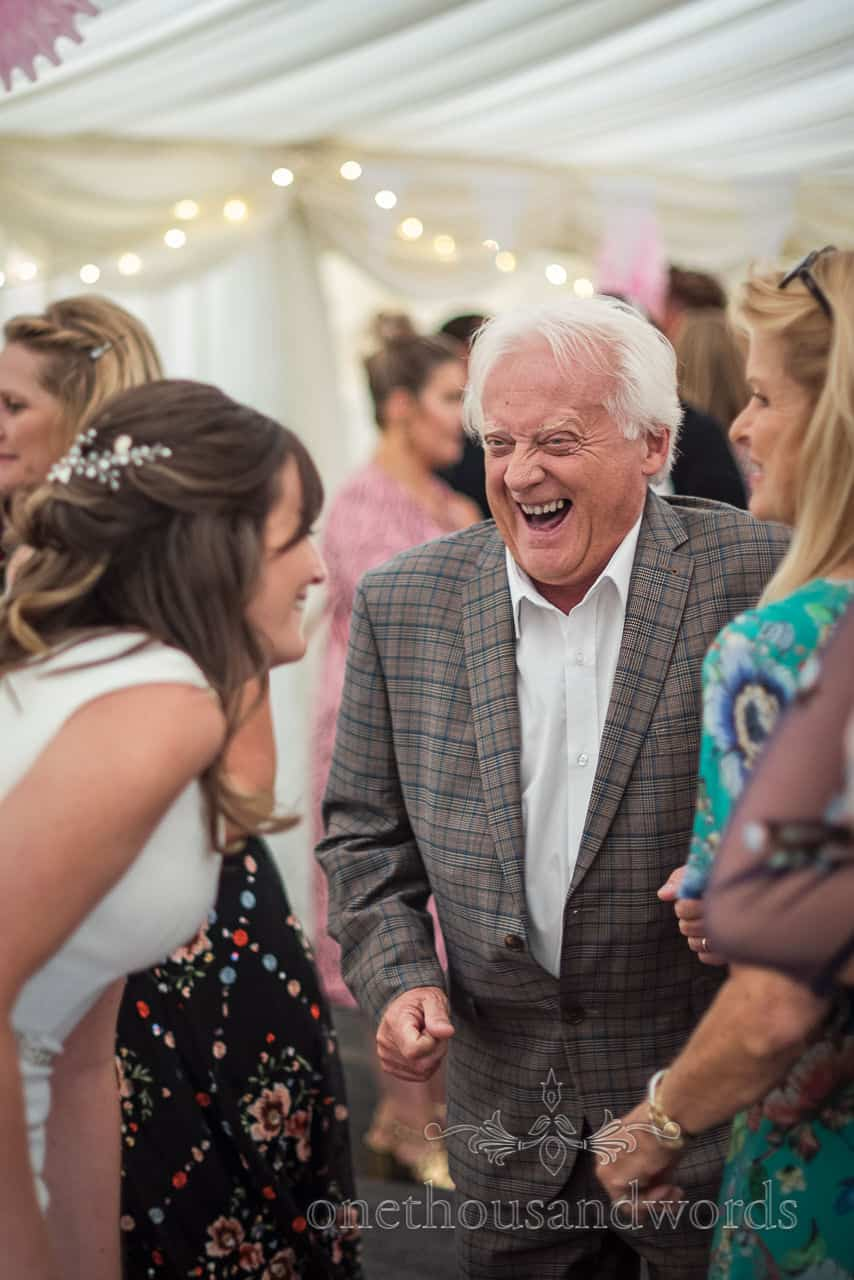 Male wedding guest in cheque suit laughing with bride on the dance floor at marquee wedding photograph