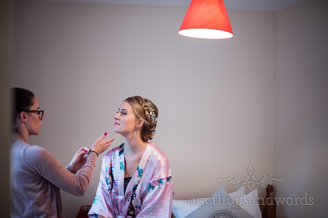 Documentary wedding photograph of beautiful bride having wedding make up styled by MUA on Dorset wedding morning