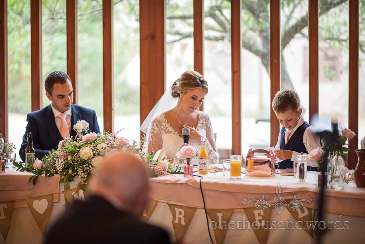 Bride uses microphone to make wedding speech from top table at barn wedding at Kingston Country Courtyard in Dorset