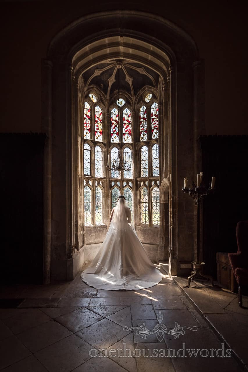 Bride in Oriel window at Athelhampton House wedding venue by one thousand words wedding photography