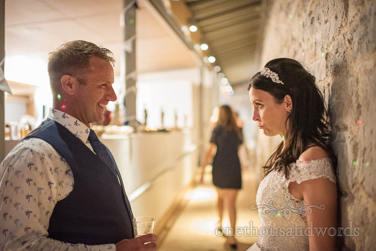 Bride pulls funny face at laughing groom during wedding evening reception photograph by one thousand words wedding photography