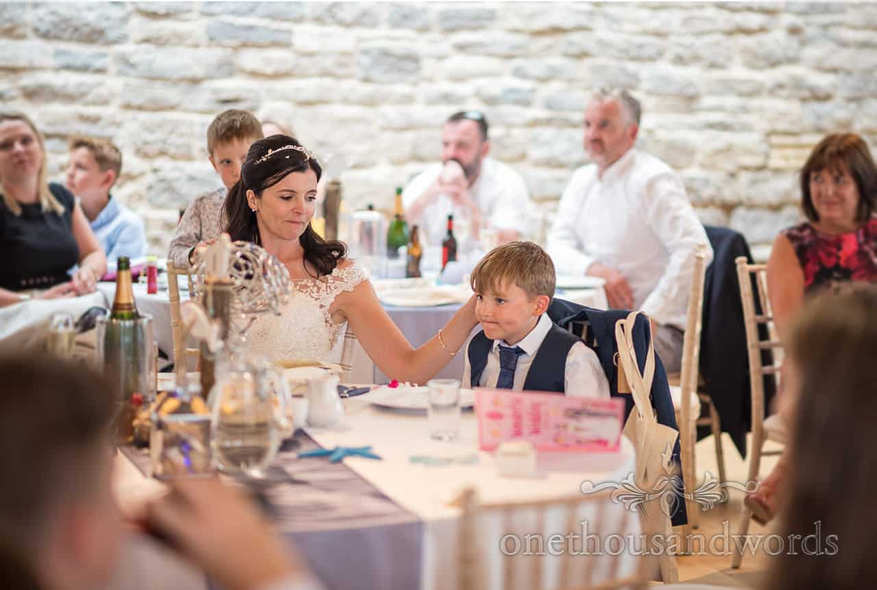 Bride strokes her child son's head during emotional wedding speeches surrounded by wedding guests at wedding breakfast