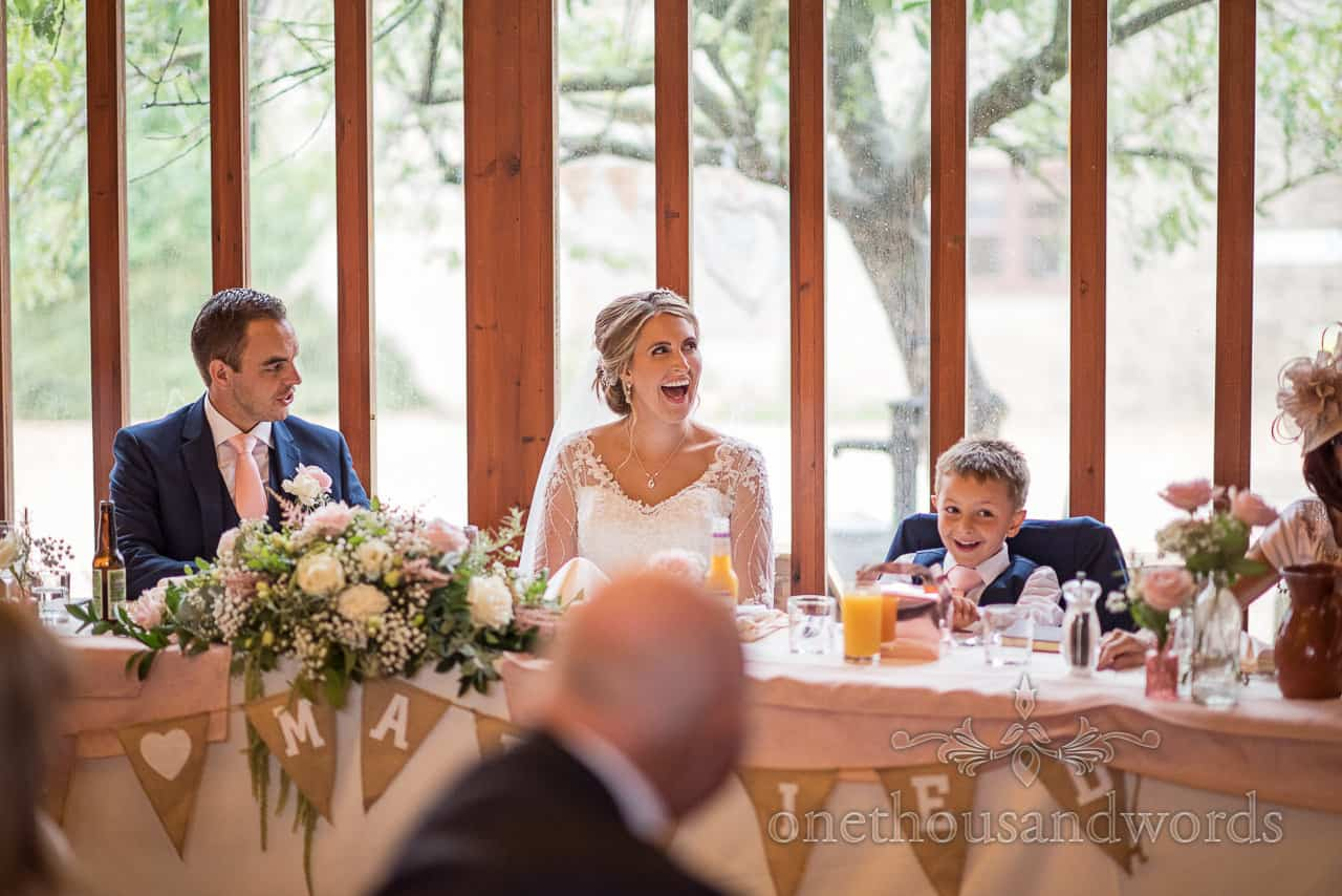 Brides and page boy son's laughing reaction to Kingston courtyard barn wedding speeches at top table with flowers and bunting