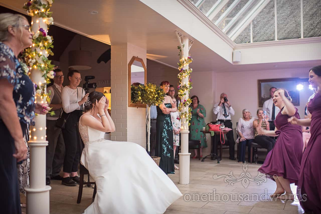 Bride reacts with her head in hands to surprise song and dance performance by groom and wedding guests at Athelhampton House wedding