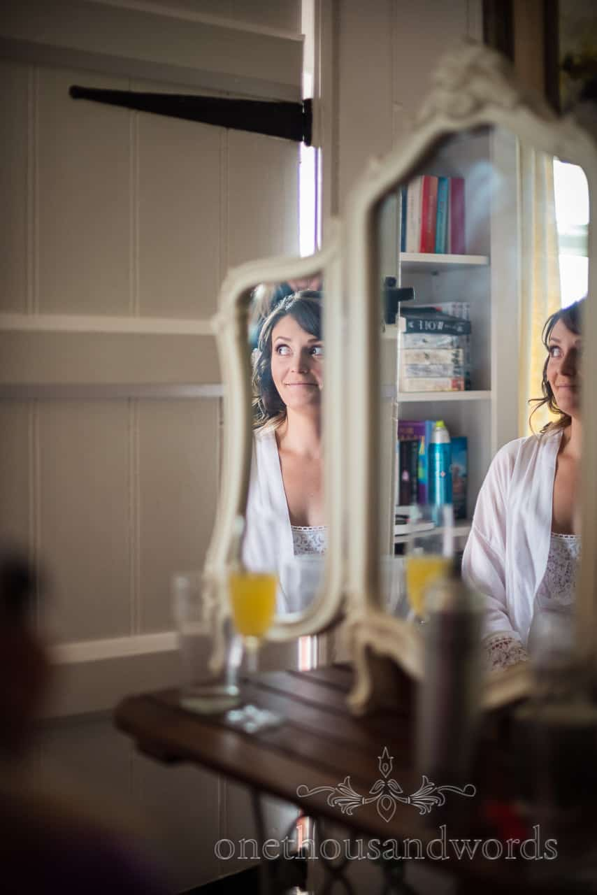 Documentary wedding photograph of bride's funny face reflection in dressing table mirror on wedding morning preparations