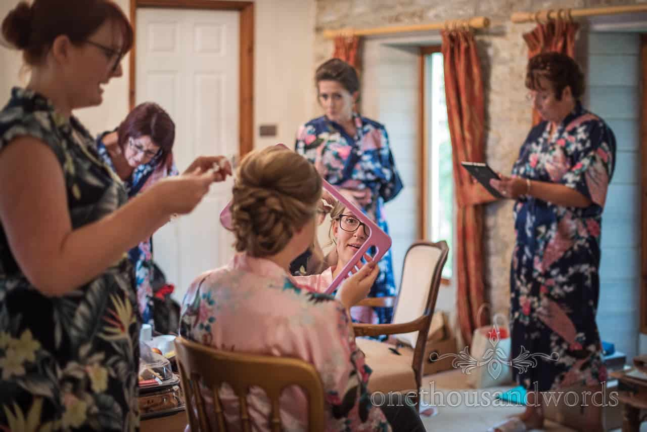 Bride's reflection in hand held mirror as wedding hair is styled on wedding morning with bridal party in matching dressing gowns
