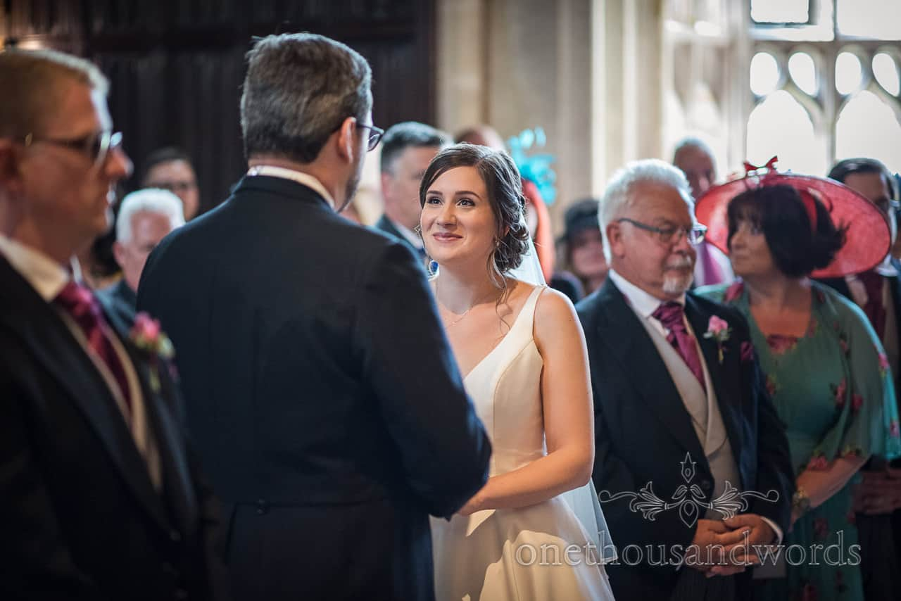 Bride smiles at groom during wedding ceremony vows surrounded by family and friends documentary wedding photograph