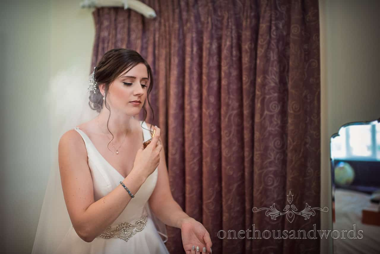Stoic looking bride in wedding dress sprays perfume during wedding morning preparation photograph by one thousand words photography