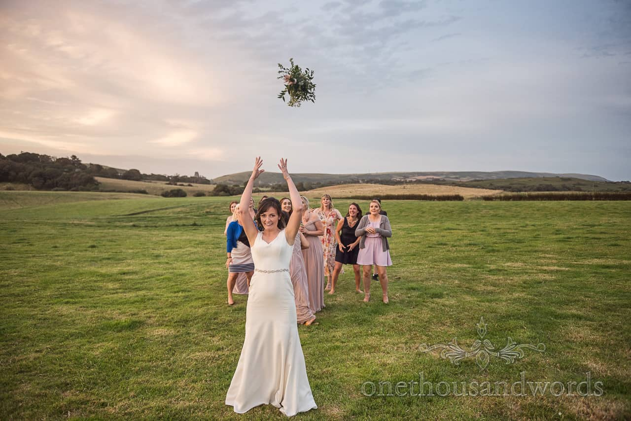 Bride throws bouquet to a group of female wedding guests in a field at Purbeck farm marquee wedding photographs