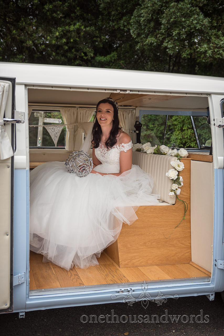 Smiling bride holding Refinerii Bridal metal wedding bouquet sits in blue and white retro classic VW wedding camper van