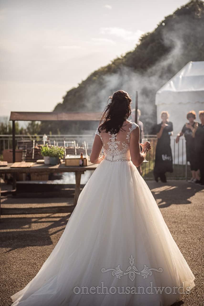 Bride in white wedding dress walks towards smoking wedding food at Purbeck Castle wedding drinks reception