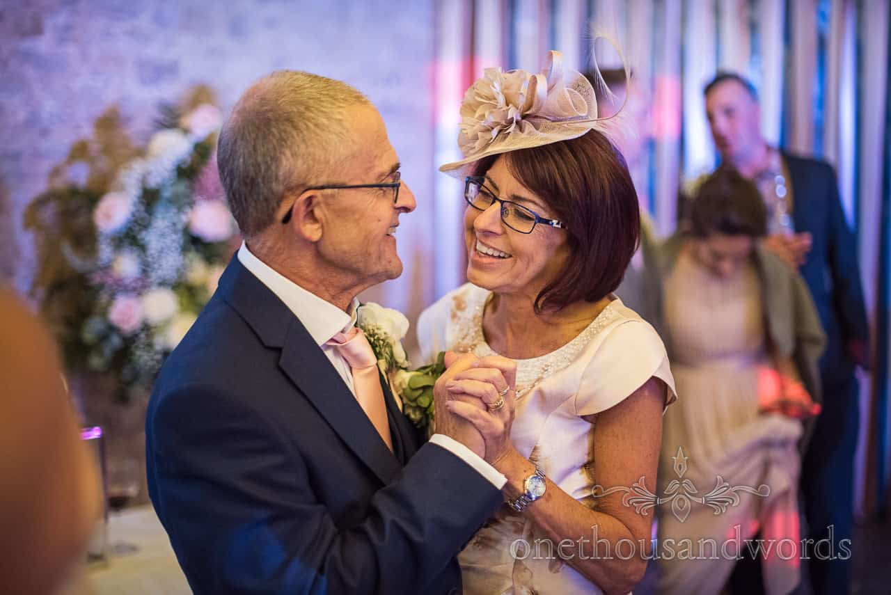 Father and mother of the bride dance together during wedding evening reception barn wedding photographs