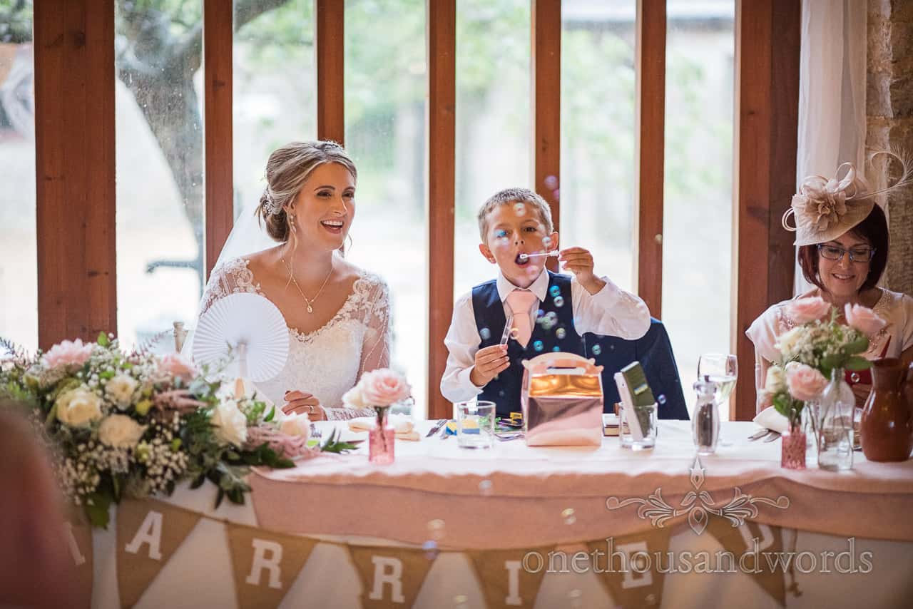Bride's son page boy blows bubbles from wedding top table at Kingston Country Courtyard wedding venue in Dorset