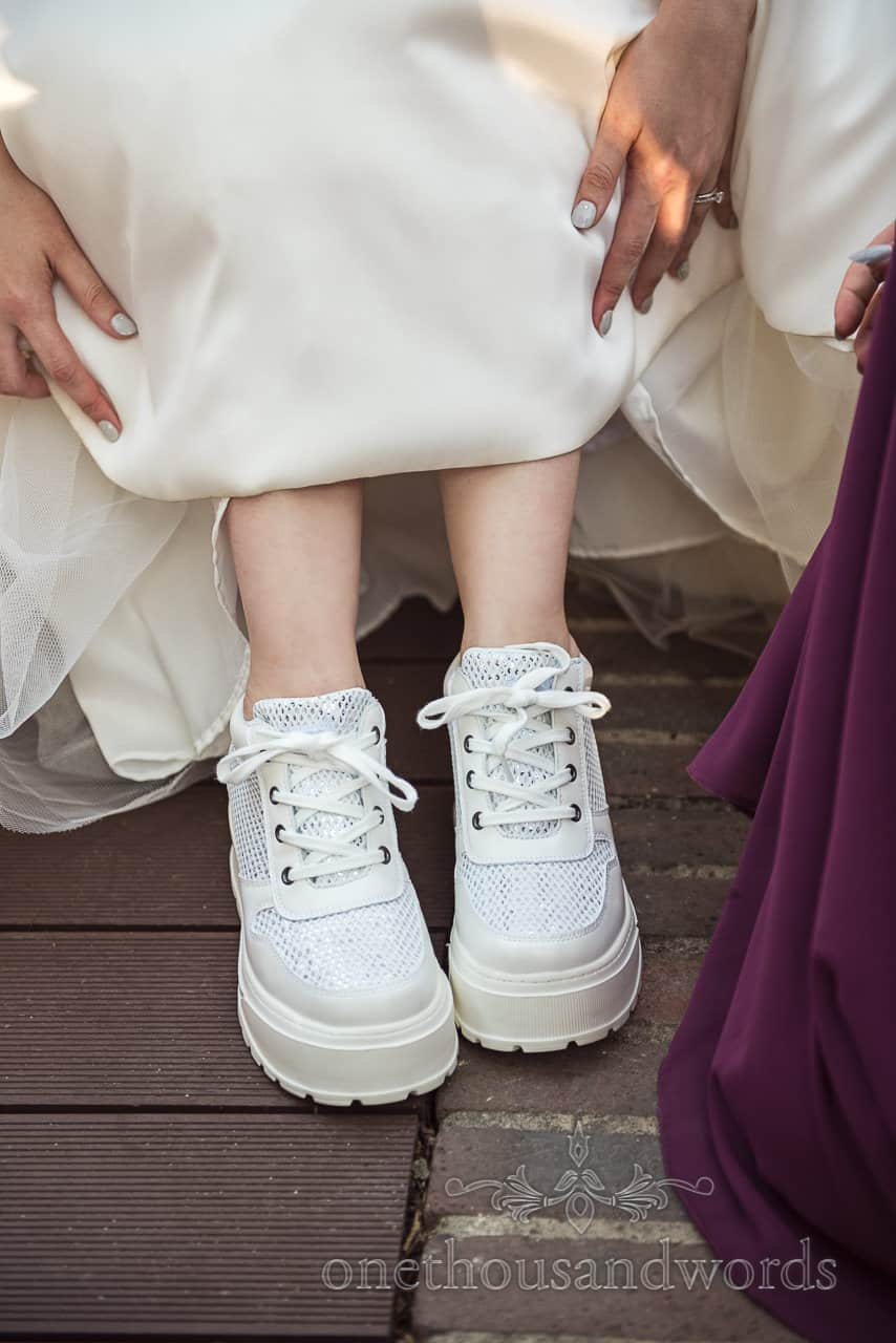 Bride shows off white diamanté trainers with thick soles under her wedding dress
