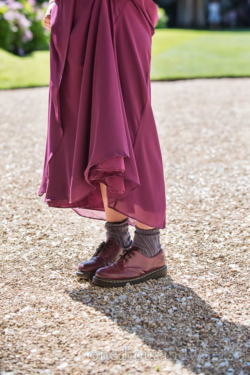 Bridesmaid wears berry dress with purple Doctor Martin's Shoes standing on gravel at wedding