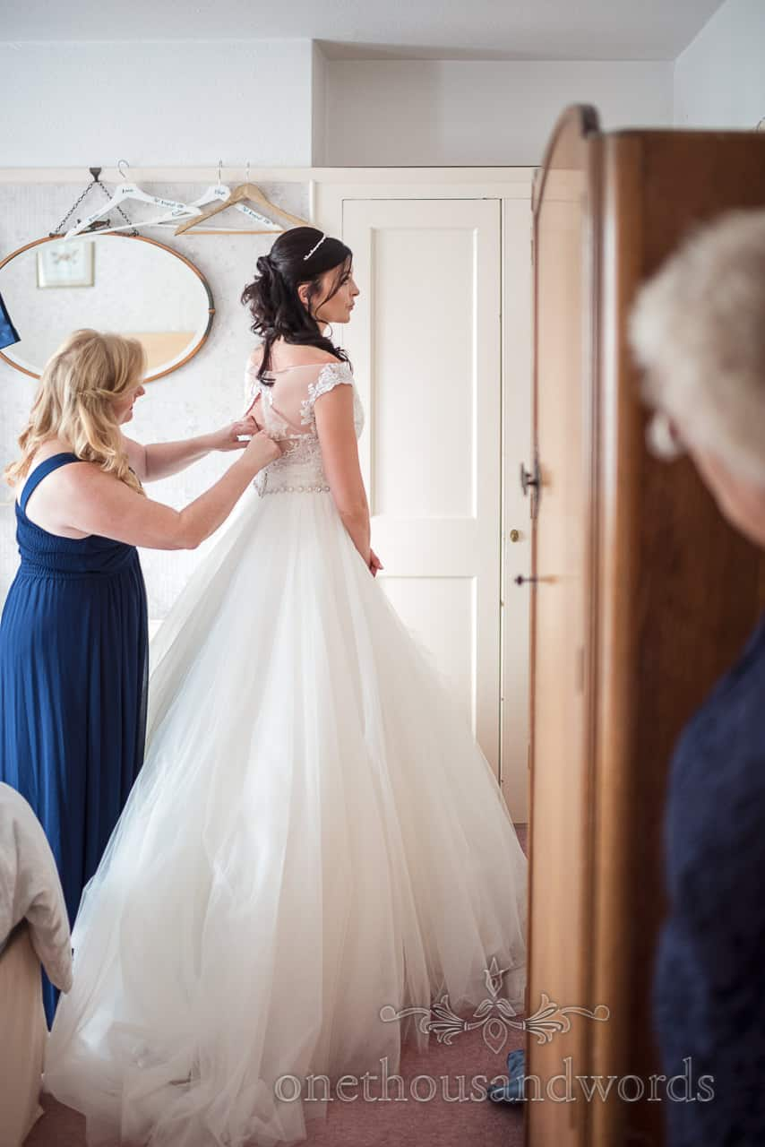 Bridesmaid buttons bride into her white wedding dress watched by the mother of the bride during wedding morning preparation photos
