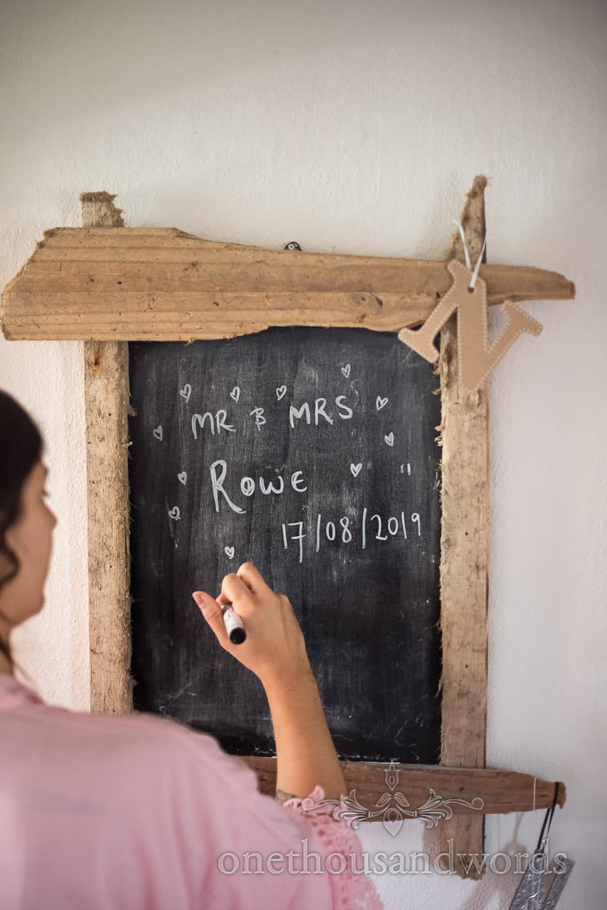 Bridesmaid writes bride and groom's names and wedding date on chalkboard framed with reclaimed wood on wedding morning