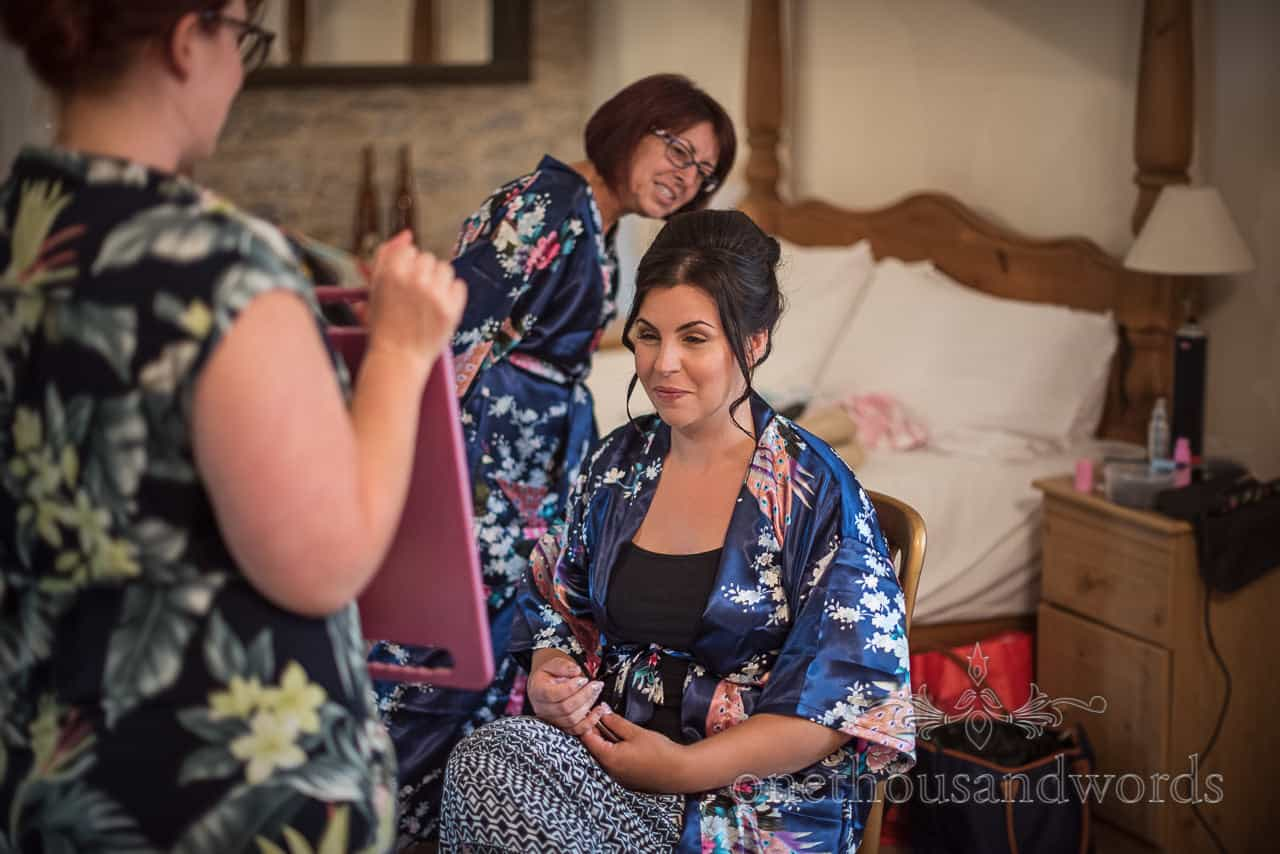 Bridesmaid checks her reflection of wedding make up and hair styling in mirror on wedding morning preparations in Dorset